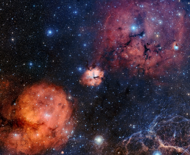 This wide-field view captures the spectacular celestial landscape around the central object Gum 15. Among many other objects the star cluster NGC 2671 is visible a little to the lower left of centre and at the lower right of the image some of the filaments forming part of the Vela Supernova Remnant can be seen. This view was created from images forming part of the Digitized Sky Survey 2.
